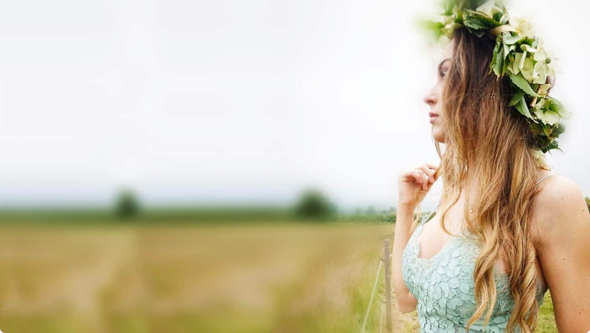 Woman with flowers in her hair looking out on a field